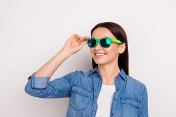 Portrait of young pretty woman in casual jeans shirt touch green glasses and have fun isolated on white background