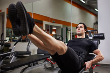 Full length portrait of muscular build man while doing legs press exercise in fitness center.