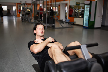 Full length portrait of muscular build man while doing push up exercise in fitness center.