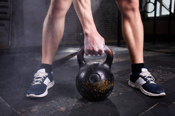 Closeup photo of young man's legs in sneackers and arm while keeping kettlebell against dark background.