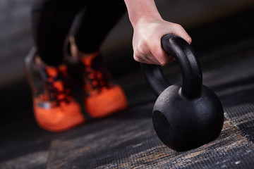 Closeup photo of young woman in the black leggings and orange sneackers while push-ups with kettlebell.