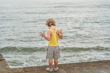 Cute boy stands on the shore watching the ocean waves