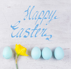 Row of blue eggs with yellow daffodil on aged wooden table desktop with happy easter greetings