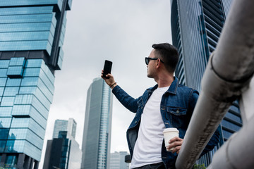 Young man taking selfie pictures in a modern business district of Jakarta