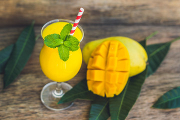 Juicy smoothie from mango in glass with striped red straw and with a mint leaf on old wooden background. Healthy life concept, copy space