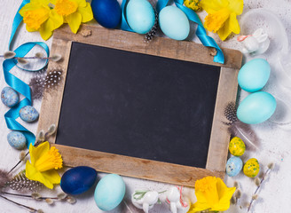 Easter frame with painted blue eggs and flowers and empty chalkboard with copy space