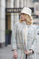 Beautiful stylish blond woman in coat and hat on city street.
