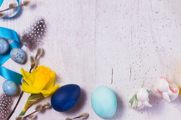 Easter border with painted blue eggs, rabbits and flowers on aged wooden desktop