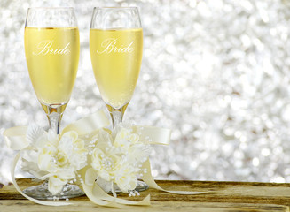 A pair of glasses filled with sparkling bubbly champagne and decorated with ivory colored satin ribbons and silk flowers on a wooden table in front of a sparkly, glittering silver bokeh background