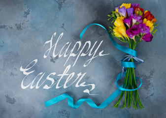 Mix of fresh freesia flowers on gray stone background with with happy easter greetings