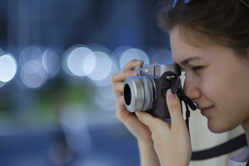 Young girl with a vintage looking camera taking photos outdoor.