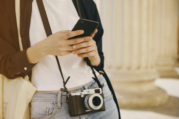 Young girl with a smart phone and a vintage camera