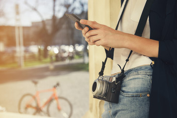 Hipster concept: young girl with a camera using her smart phone