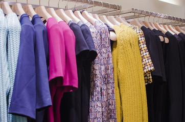 Women clothes on racks in a fancy store.