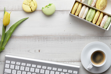 Woman's flat lay workspace with keyboard, macarons, yellow tulips and a cup of coffee