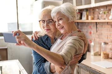Cheerful old women making selfie in kitchen