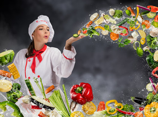 Young woman chef blowing fresh vegetable