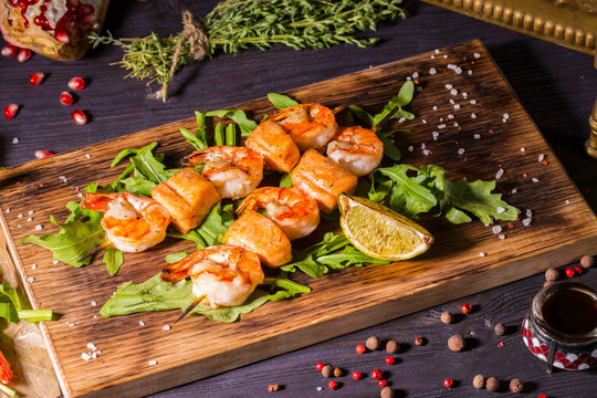 Salmon shish kebab and shrimps, is served with leaves of arugula and a lime