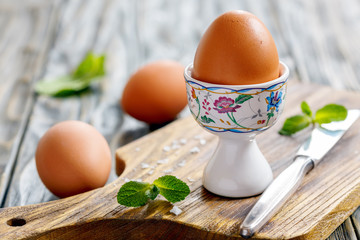 Boiled brown egg on a stand.