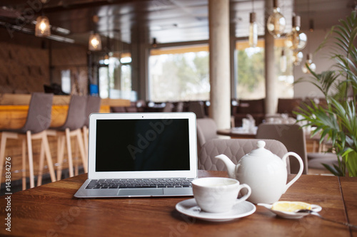 Open Net Book And Cup Of Tea With Lemon On Table In Moder Cafe Restaurant