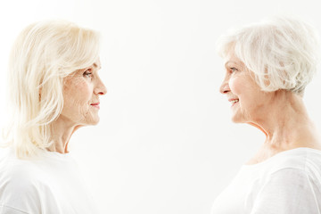 Joyful mature female friends are satisfied by their appearance