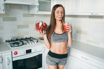 Girl drinking strawberry smoothie on the kitchen.