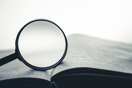 Magnifying glass on open book background. Empty copy space inside.