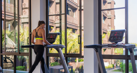 Woman running on the treadmill in the gym with a great poolside view