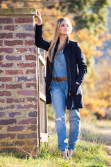Senior photo of a young woman on a farm wearing farm style clothing
