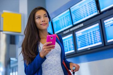 Travel woman using smartphone at airport. Young asian traveler checking boarding time with mobile phone app in terminal or train station. Tourist on vacation.