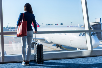 Woman looking at window in airport. Unrecognizable tourist relaxing at lounge looking at airplanes while waiting at boarding gate before departure. Travel lifestyle.