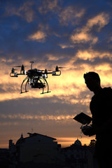 pilot is flying the drone with the camera with skyline city sunset background