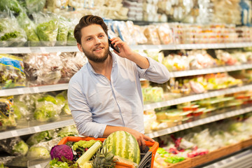 Bearded young man talking on his phone while shopping