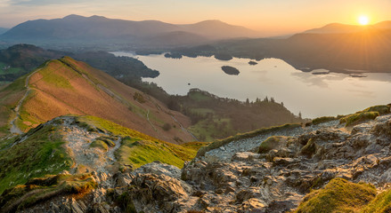 Sun rising above horizon at Derwentwater illuminating the landscape with vibrant Spring light. Wall mural