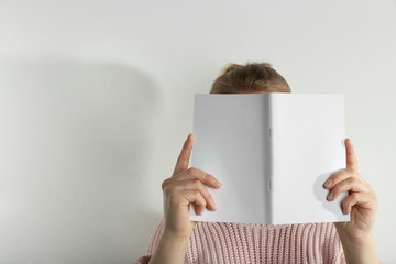 Woman holding blank open brochure on white background