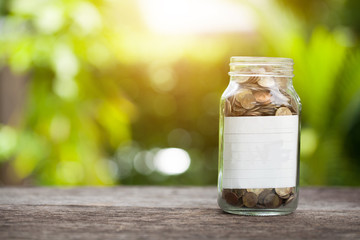 Stack of coins in saving money jar with note paper isolated on naturel background, concept saving money.