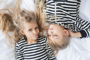 girl with white curly hair in a striped vest and a  boy with blond hair in a striped vest sleeping in bed. Children having fun.Children pretending to sleep. Children covered their faces with hands