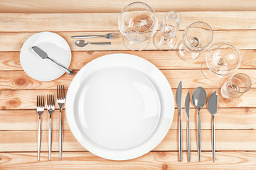 Beautiful table setting with white plates on wooden table