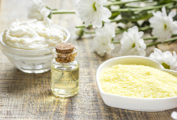 natural essential aroma oil with camomile on wooden table background