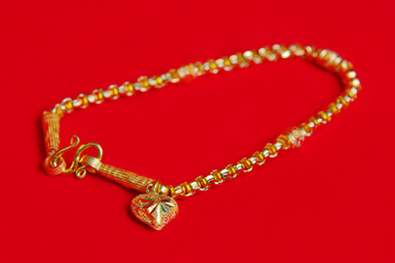Gold necklace 96.5 percent Thai gold grade with gold heart pendant isolated on red flannel cloth background