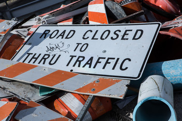 A dump of Road Closed Sign fell down on a road with broken barricades pile of metal and pipes close to construction zone. Miami. Florida. USA