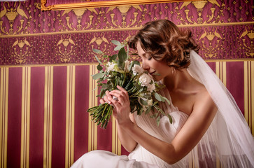 Beautiful bride with gorgeous flowing curls. In a pretty white lace wedding dress with a romantic bouquet of peonies, roses, sitting in a luxury burgundy interior, fashion photo portrait.