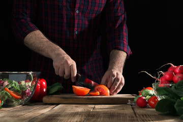 Man preparing salad with fresh vegetables on a wooden table