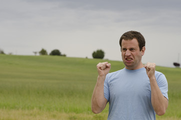 Furious man with clenched fists outside in the countryside.