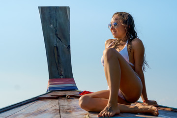 Young smiling caucasian woman resting on a boat on a sunny day