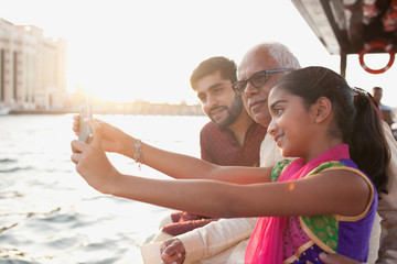 Girl talking selfie with family at Dubai Creek.