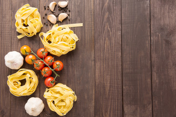 Pasta ingredients. tomato, garlic and pepper on wooden background