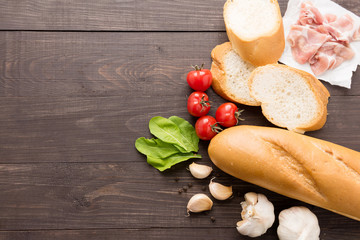 Ingredients for sandwich with smoked meat, baguette on wooden background