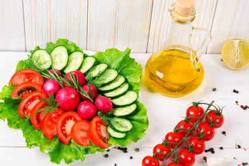Cucumbers, radish, tomatoes cherry, olive oil, herb and spices on old white wooden background. Set for healthy foods. Ingredients for salad