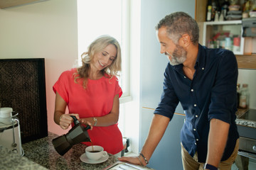 Man with woman pouring coffee at kitchen.
